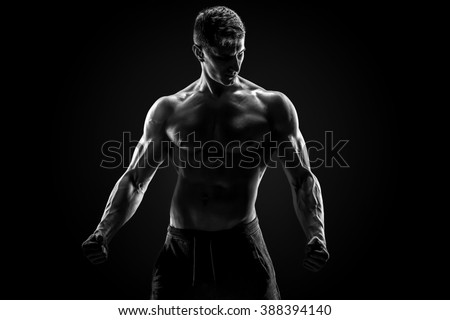 Sexy muscular man posing with naked torso on black background - stock photo