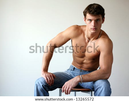 Sexy muscular man sitting on the chair. Copy space