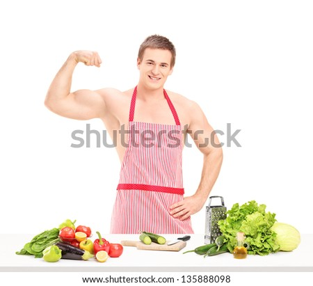 Sexy muscular man wearing a red apron and preparing a salad, isolated on white background - stock photo