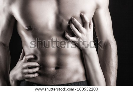 Sexy muscular naked man and female hands on a dark background - stock photo