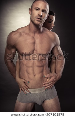 Sexy muscular naked man and female hands on his torso - stock photo