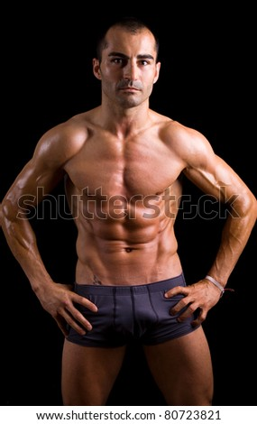 Sexy muscular young man against black background
