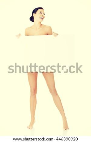 Sexy naked brunette holding empty board - stock photo