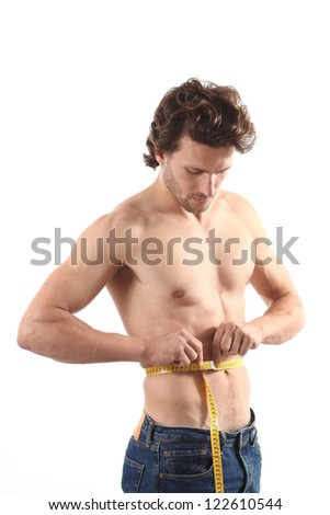 Sexy naked man measuring his waist with a measure tape on a white isolated background