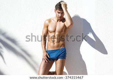 Sexy naked model with athletic body wearing blue beach shorts and posing on white wall