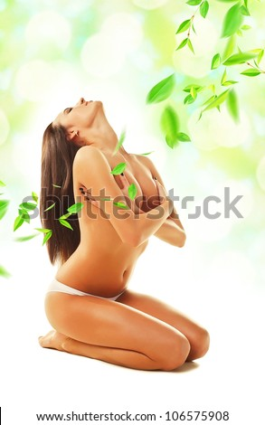 sexy naked woman siting on the floor with leaves - stock photo