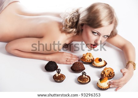 sexy naked woman with long blond hair laying down on white with some pastry near her in act to eat them, she looks in to the lens and her right arm is around the pastries