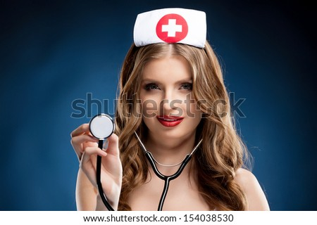 Sexy nurse. Beautiful young nurse in uniform holding stethoscope while standing isolated on colored background - stock photo