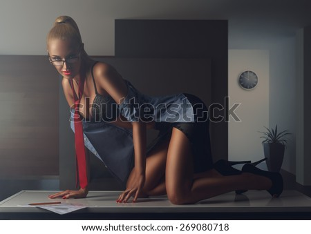 sexy office secretary in unbuttoned shirt posing on the table - stock photo