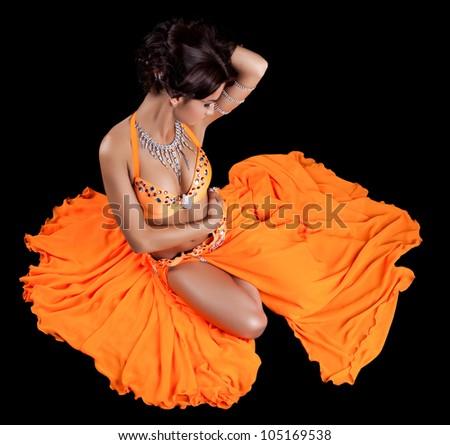 Sexy oriental dancer in orange costume - stock photo