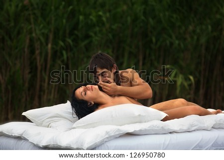Sexy passion between two lovers in bed against cane - stock photo