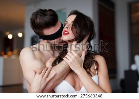 Sexy passionate couple foreplay at home, sexy macho man in lace eye cover, bdsm - stock photo