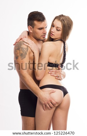 Sexy passionate heterosexual couple hugging on white isolated background