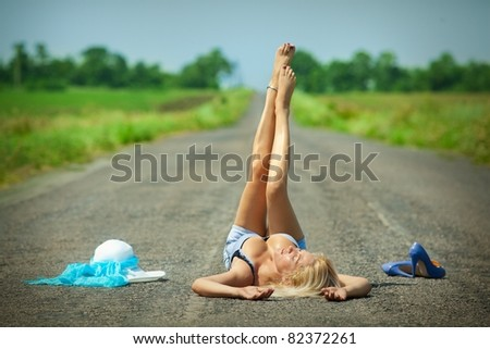 Sexy passionate woman lying on a desert road