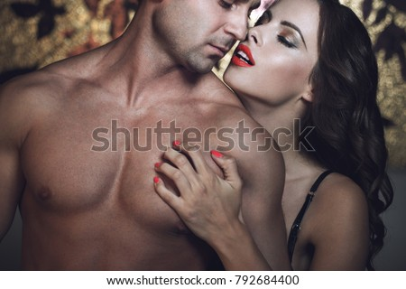 Sexy passionate woman playing with muscular lover at night closeup