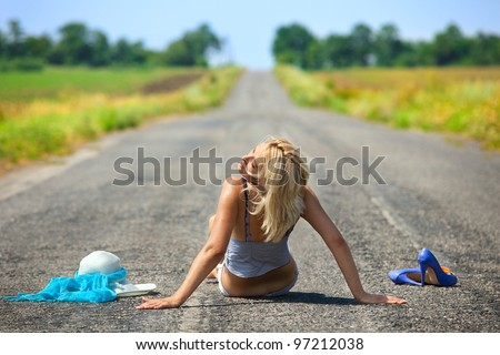 Sexy passionate woman sitting on a desert road - stock photo