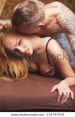 Sexy passionate young heterosexual couple embracing on the bed - stock photo
