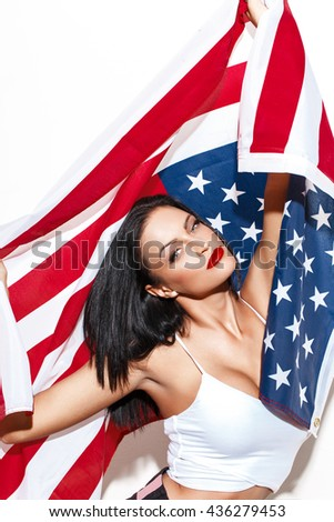 Sexy patriot brunette woman holding USA flag at white wall, patriotism