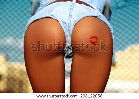 Sexy perfect female woman buttocks ass on blue sky city outdoors background with red kiss in jeans shorts - stock photo