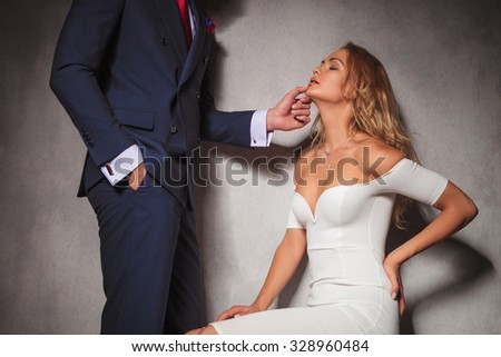 sexy picture of a gentleman holding his woman by her chin, she is sitting in studio. hot sensual couple in studio - stock photo