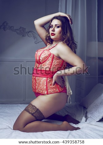 sexy plus size model wearing a corset in the bedroom - stock photo