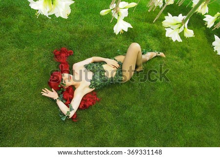 Sexy poison ivy leafs made bodysuit cosplay girl lying under lily blossoms at flower exhibition. - stock photo