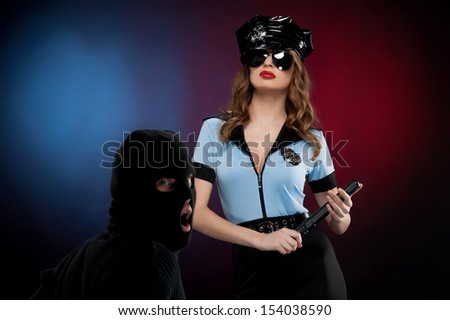 Sexy policewoman at work. Beautiful young policewoman in uniform standing close to the man in black mask while isolated on colored background - stock photo