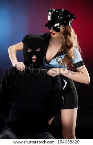 Sexy policewoman at work. Beautiful young policewoman in uniform standing close to the man in black balaclava while isolated on colored background - stock photo
