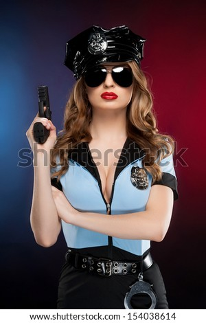 Sexy policewoman. Beautiful young policewoman in uniform holding a gun while standing isolated on colored background - stock photo