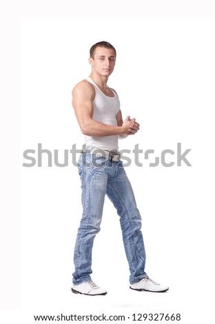 Sexy portrait of a hot male model in stylish jeans with muscular body posing in studio on white - stock photo
