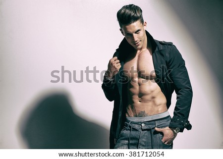 Sexy portrait of a very muscular male model in sensual pose. Fashion colors. - stock photo