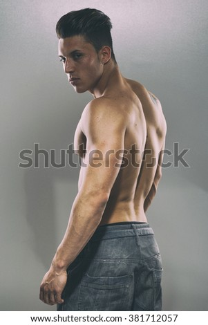 Sexy portrait of a very muscular male model in sensual pose. Fashion colors.