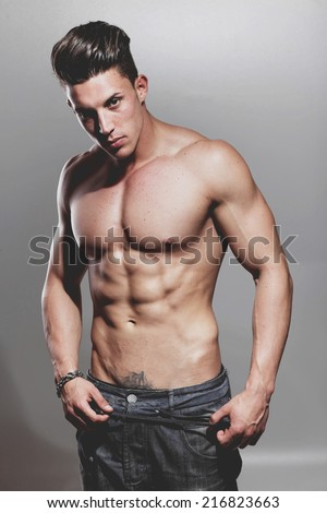 Sexy portrait of a very muscular shirtless male model against grey wall in sensual pose