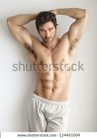 Sexy portrait of a very muscular shirtless male model against white wall in sensual pose