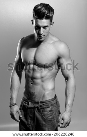 Sexy portrait of a very muscular shirtless male model against white wall in sensual pose. B&W
