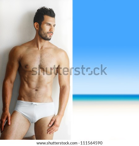 Sexy portrait of a very muscular shirtless male model in underwear against white wall in sensual pose with tropical paradise in background - stock photo
