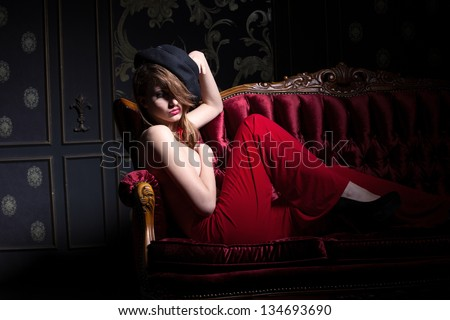 Sexy posing girl hiding her face with the hat, studio shot - stock photo