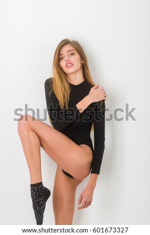 sexy pretty girl or beautiful woman with long, blond hair, hairstyle, in black bodysuit has young face isolated on white background