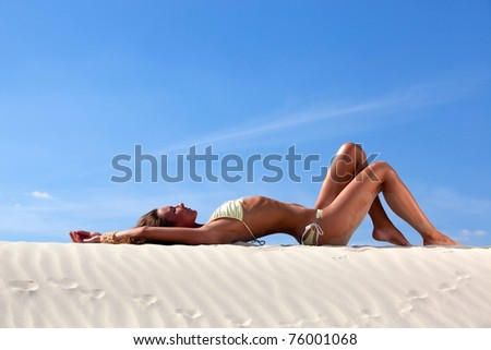 Sexy pretty woman in bikini sunbathing at the beach