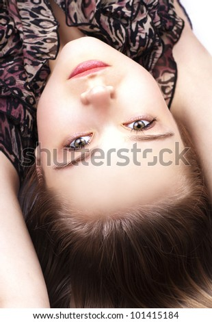 Sexy pretty woman lying on the floor, close up, hands up - stock photo