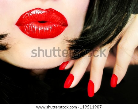 Sexy pretty woman with black hair, red lips and fingernails sending a kiss / smooch - closeup