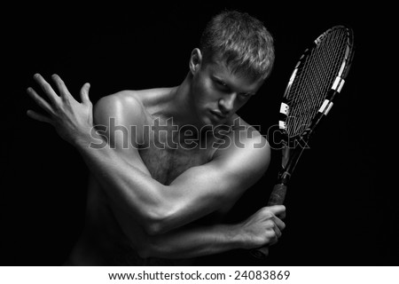 Sexy racket. A portrait of a tanned sportive tennis player with a racket against black background.