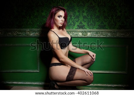 Sexy readhead in provocative lingerie on green vintage wall. Sexuality and sensuality. Beauty and lingerie - stock photo