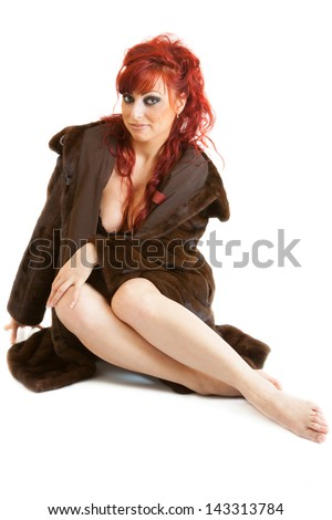 sexy red-haired young woman wearing underwear and  mink fur coat sits - stock photo