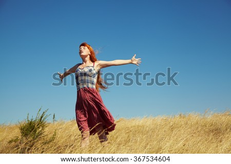 sexy redhead woman in a dress outdoors. Beautiful stylish romantic young girl on nature background. field and clear cloudless sky - stock photo