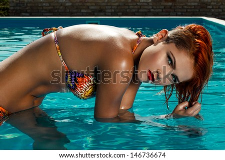 Sexy redhead woman in bikini playing with hair in the water, high fashion - stock photo