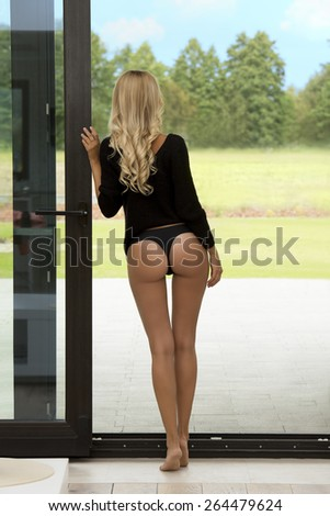 sexy relaxed blonde girl with sensual body, black sweater and naked legs turned on her back posing in home on the threshold of garden  looking outside - stock photo