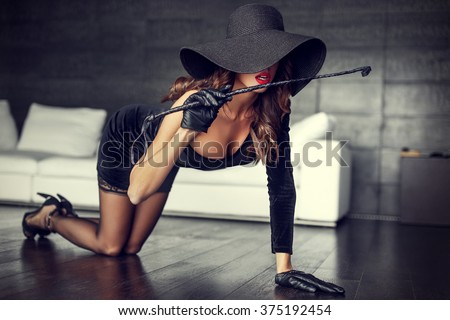 Sexy rich woman in hat and whip kneeling on floor indoor - stock photo