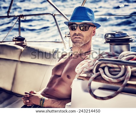 Sexy sailor, man on sailboat enjoying cruise, vintage style photo of a handsome shirtless model sailing on a luxury water transport, fashion lifestyle concept - stock photo