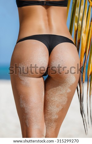 Sexy sandy woman buttocks on tropical beach background near ocean. close up outdoor shot of young woman in white bikini, sunbathing at sea shore. Black bikini near pal leaf